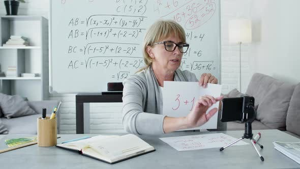 Thumbnail for Female Math Teacher Sitting At The Desk. She Conducts An Online Lesson
