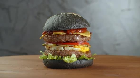 Thumbnail for Burger oder Hamburger mit Schwarzbrot auf einem verschwommenen Hintergrund der Blätter
