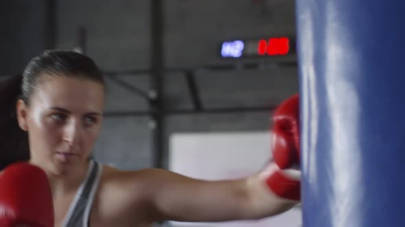 Female Boxer Punching Heavy Bag and Looking at Camera