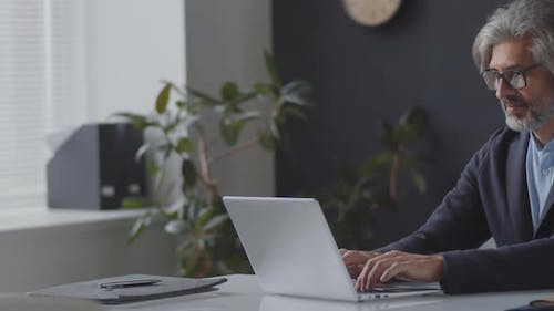 Mid-Aged Businessman Working on Laptop in Office