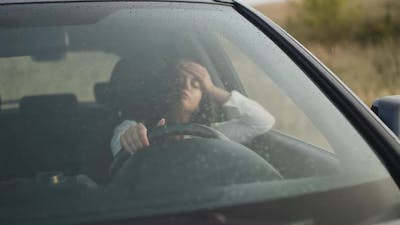 View Through the Windscreen of Worried Girl in Car is Nervous and Waits