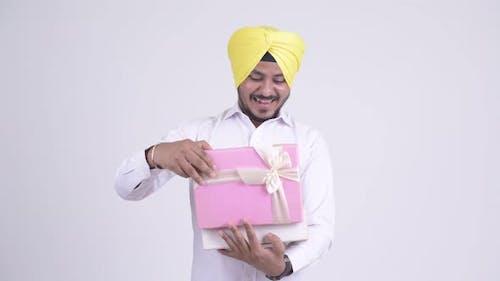 Happy Bearded Indian Sikh Businessman Opening Gift Box