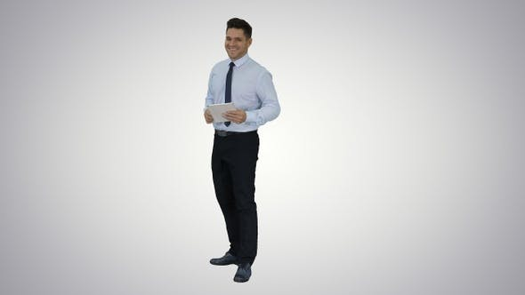 Happy businessman walking in and using tablet turning on