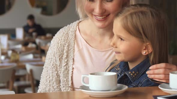 Thumbnail for Woman Shows Her Daughter Something at the Cafe