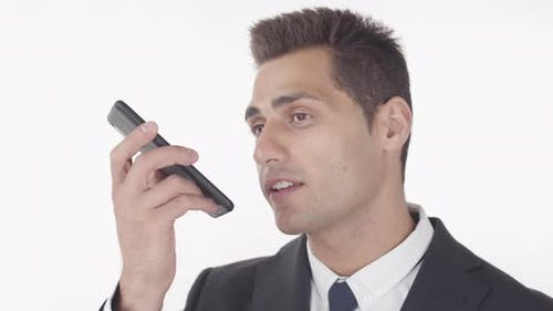 Attractive Man Recording Voice Message Using Telephone