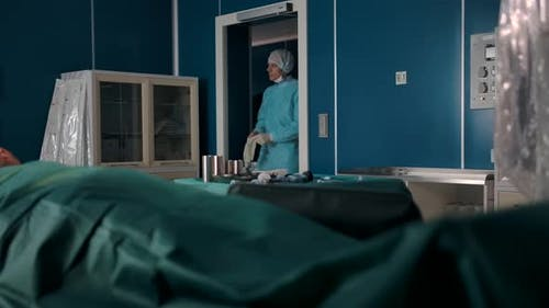 Two Professional Surgeons in Uniforms Gloves Masks and Hats Enter the Operating Room