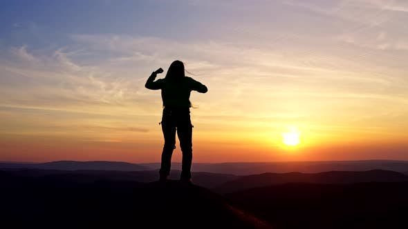 Silhouette of a Young Woman Dancing on a Mountain Top at Sunset