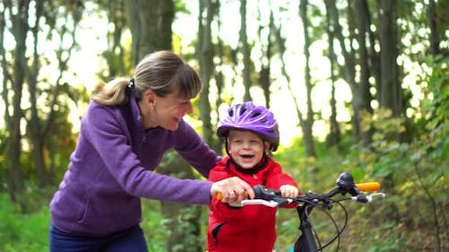 Closeup. Mama teaches her little son to ride a bike. Happy boy. Moving camera.
