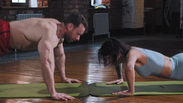 Couple in the Gym  Doing Push Ups Together on Yoga Mats and Doing a Clap to Each Other