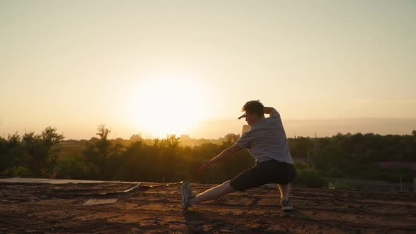 Silhouette of a man practicing martial arts on the background of a beautiful sunset.