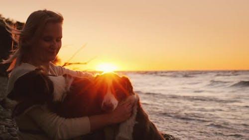 Glücklicher Besitzer von zwei Hunde spielen mit Haustieren am Strand bei Sonnenuntergang