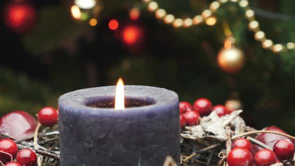Beautifully decorated christmas table with candle against Christmas tree.