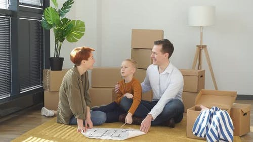 Relaxed Family With Child Boy Sit On Floor Talking Planning Their Home Interior Moving Into New