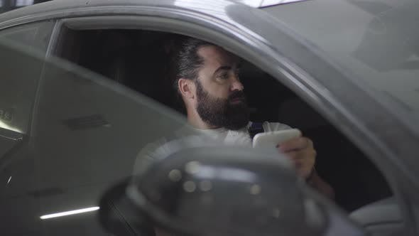 Thumbnail for Professional Mechanic Sitting Inside the Car and Verifies Information on His Phone. Bearded Man in