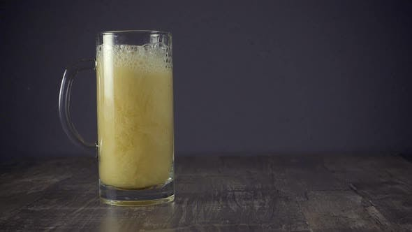 Thumbnail for Slow Motion Pour Light Beer in a Mug on a Grey Background