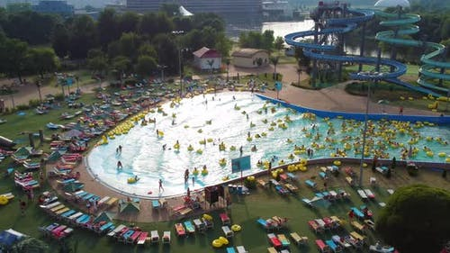 Summer day in the city water park, people have a rest, swim on inflatable rings.