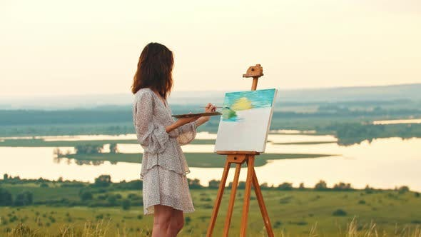 Young Woman with Dark Hair Drawing a Painting on Sunset and Looks in the Camera