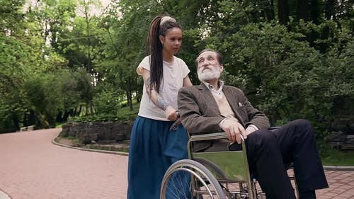 Granddaughter with Dreadlocks and Respected Bearded Senior Granddad in Wheelchair Walking