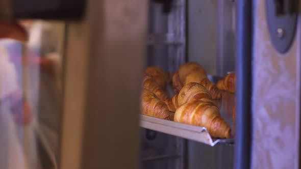 Thumbnail for The Pastry Chef Opens the Oven with Freshly Baked Croissants. Fresh Pastries.