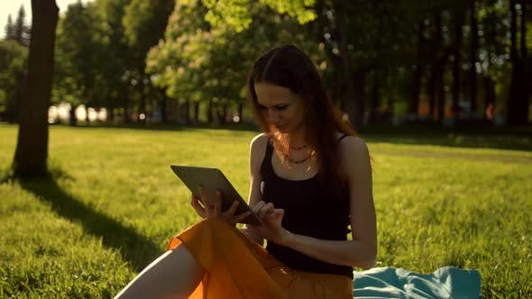 Thumbnail for Young Lady Browsing Her Tablet in the Park.
