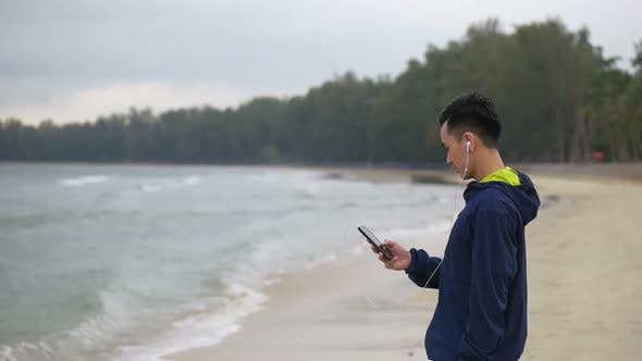 Handsome man running using smartphone on the beach, Asian man running on the beach.