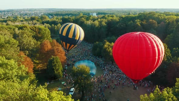 Thumbnail for Aerial View of Red Hot Air Balloon Takes Off Among the Trees in the Park. Beautiful Sky and Sunset