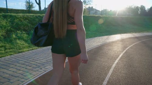 Woman Carrying Bag at Stadium Before Training