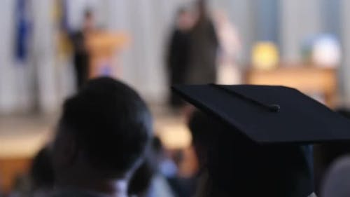 Girl Wearing Mortarboard Looking at Stage and Listening Rector's Congratulations