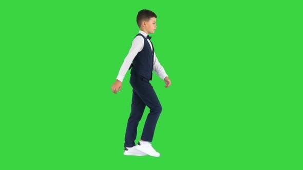 Kleiner Junge in einer Fliege und Weste, der mit den Händen auf einem Green Screen Chroma Key winkt