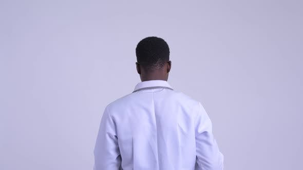 Thumbnail for Rear View of Young Happy African Man Doctor Directing While Holding Clipboard