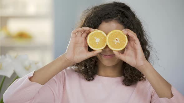 Thumbnail for Mixed Race Girl Smiling at Camera, Holding Halves of Oranges Before Eyes, Health