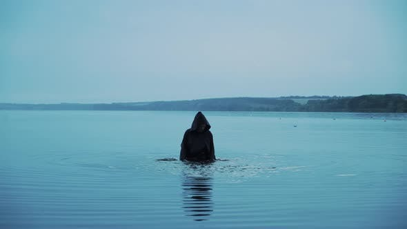Terrible figure in a black robe in the water outdoor