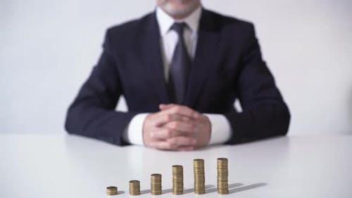 Wohlhabender Mann sitzt vor Münzstapel, Wachstum der Einlagen-Zinsen, Banking