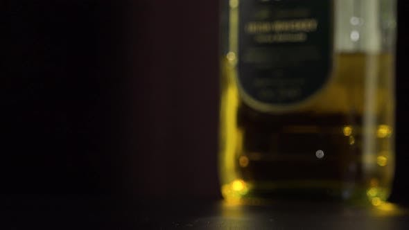 Thumbnail for A Man Lifts a Glass of Whiskey From a Table - Closeup - a Bottle in the Blurry Background