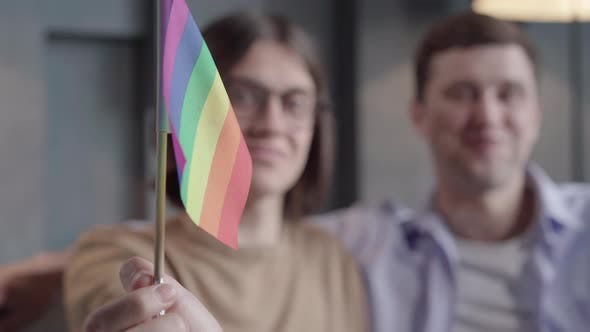 Thumbnail for Close-up of Rainbow Lgbt Flag in Male Hand with Two Blurred Men Smiling at the Background. Positive