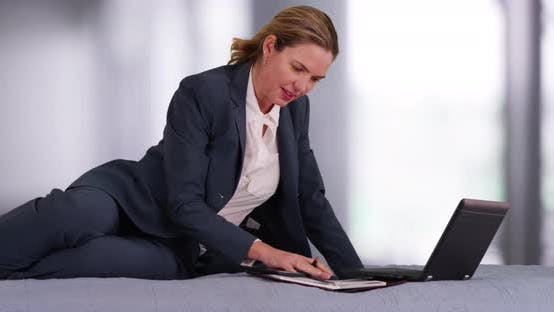 Thumbnail for Professional woman in business suit working on laptop and cellphone from bedroom