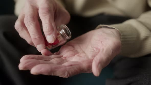 Man Hold Many Multicolored Pills in a Senior's Hands Antibiotic and Vitamin Drugs