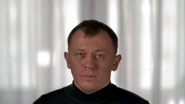 Portrait of a sad young man looking at the camera, sad and depressive emotions