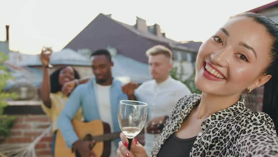 Asian Woman with Glass of Wine Making Selfie on the Background of Friends on Terrace