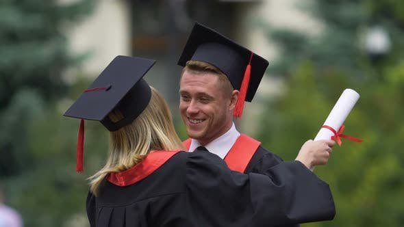 Thumbnail for Male and Female Graduates in Academic Caps Hugging, Friends Sorry to Say Goodbye