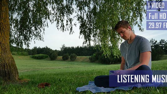 Thumbnail for Young Man Listens To Music In The Park
