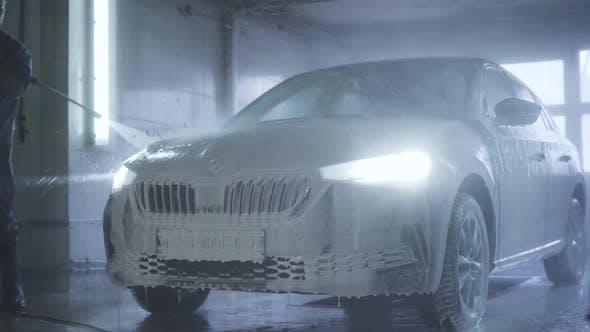 Thumbnail for Auto mit eingeschalteten Scheinwerfern, die im Autowaschanlagenservice stehen. Worker Abwaschen Schaum vom Fahrzeug