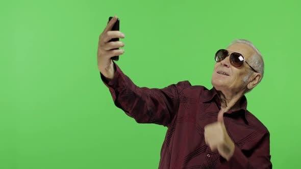 Senior Man Tourist in Sunglasses Make a Photo on a Smartphone. Selfie