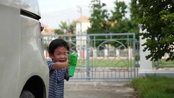 Cute Asian Child Shooting Bubbles From Bubble Gun