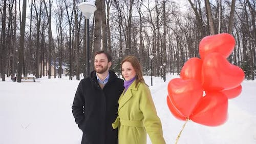 Young Cute Couple Walks in the Park with Balloons. Love Story.