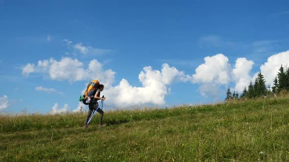 Thumbnail for Girl Hiker With The Backpack On A Grass Hill