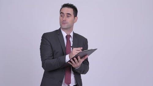 Handsome Geschäftsmann Schreiben auf Zwischenablage