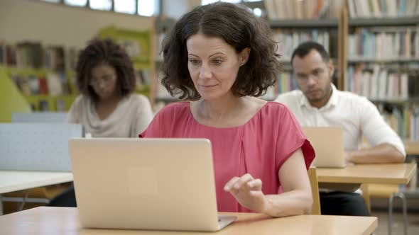 Thumbnail for Thoughtful Curly Mature Woman Working with Laptop at Library