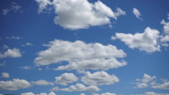 Beautiful white clouds moving fast high in the blue sky, Time-lapse. Sunny sky on a summer day`