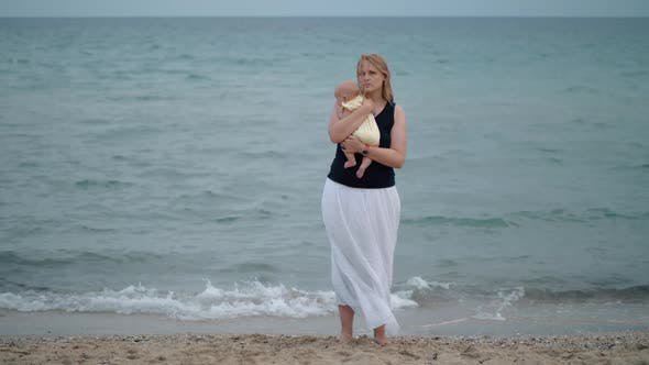 Cover Image for - Mother with Lost Look Holding Baby Being Alone at the Beach Near Sea